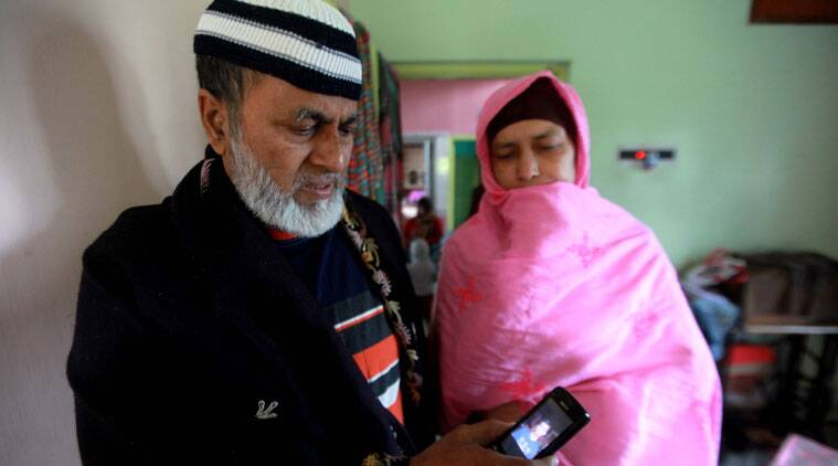 Mehdi Masroor Biswas's parents look at his picture on a mobile phone at their home in Kaikhali, near Dum Dum airport, on Saturday morning. (Source: Express photo by Subham Dutta).
