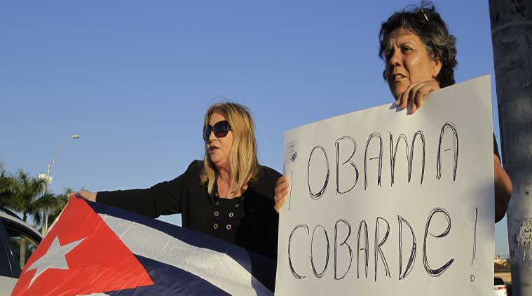 """Ana Lourdes Cuesta, left, and Liliana Cuerra protest in Miami against the Obama administration's decision to re-establish diplomatic relationships with Cuba. Cuerra holds a sign that reads """"Obama coward."""" (Source: AP)"""