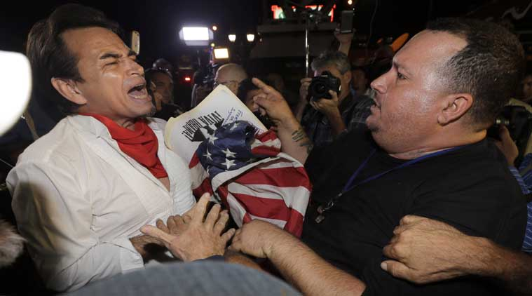 Anti-Castro protester Sisay Barcia, right, argues with pro-Obama supporter Peter Bell, left, in the Little Havana area of Miami on Wednesday. (Source: AP)