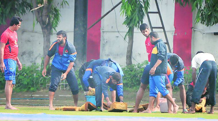 Mumbai cricketers, including captain Suryakumar Yadav and Abhishek Nayar, helped the groundstaff clear a waterlogged patch at the Karnail Singh Stadium for a little over half an hour on the second day of the Ranji match against Railways. Despite their best efforts, no play was possible on Monday. (Source: Express Photo)