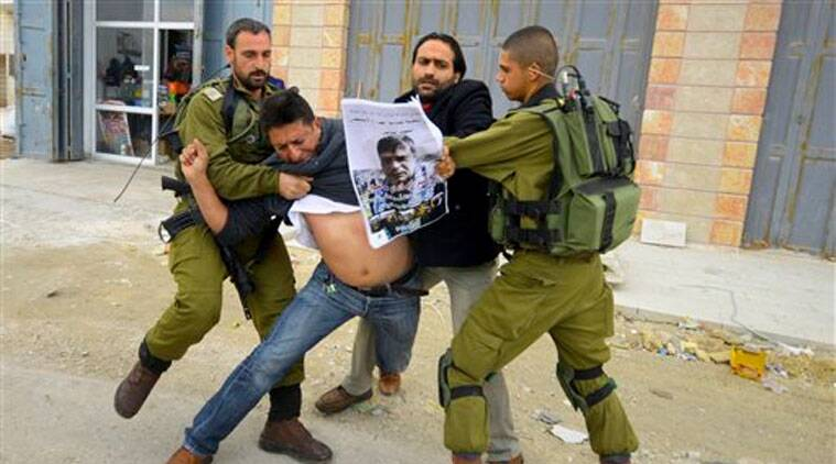 In this Friday, Dec. 12, 2014 photo, Israeli soldiers grab a Palestinian holding a poster showing late Cabinet minister Ziad Abu Ain during a protest in Bethlehem, West Bank. (Source: AP)