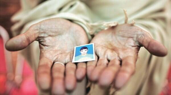 Sayed Shah holds out a photo of his son Zulqarnain, 17, who was among those killed in the Tuesday, December 16, attack. (Source: AP photo)