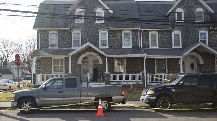 A police officer stands at the door of a crime scene at a home Monday, Dec. 15, 2014, in Souderton, Pa. A suspect was believed to have been barricaded inside after shootings at multiple homes. Police tell WPVI-TV the man is suspected of killing a five people Monday morning at three different homes northwest of Philadelphia. (AP Photo/Matt Rourke)