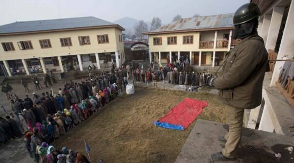 Paramilitary soldier stand guard as Kashmiris wait to cast their vote outside a polling station in Handwara, some 70 kilometers north of Srinagar. (Source: PTI photo)