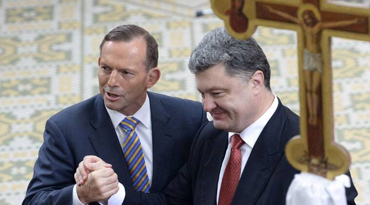 Ukraine's President Petro Poroshenko, right, and Australian Prime Minister Tony Abbott shake hands during an ecumenical church service held at Ukrainian Greek Eparchy of Saints Peter and Paul in Melbourne, Australia, Thursday, Dec. 11, 2014. Poroshenko is on a two-day visit to Australia with talks of the downing of MH17 over Ukraine with the loss of 38 Australian citizens and residents expected to high on the agenda. (Source: AP Photo/Mal Fairclough, Pool)