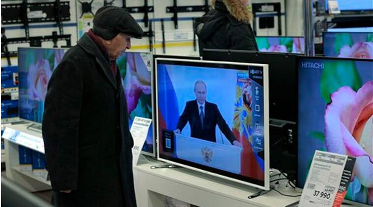 Customers look at TV sets with Russian President Vladimir Putin, at a shop in Moscow, Russia, on Thursday, Dec. 4, 2014, during his annual state of the nation address in the Kremlin.(Source:AP)