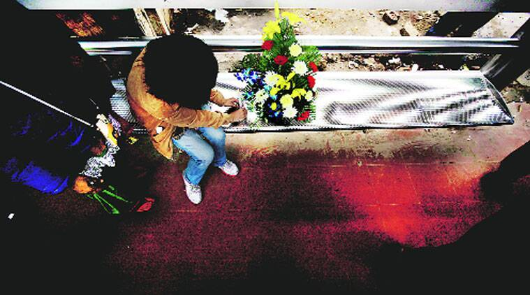 A child places flowers for the December 16 gangrape victim at Munirka bus stop on Monday. (Source: Express photo by Praveen Khanna)