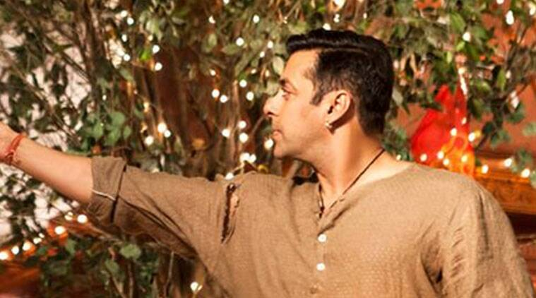 The picture shows a demure Salman, wearing a torn Kurta and feeding a monkey.