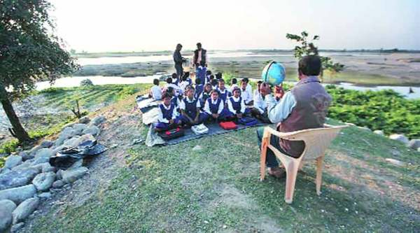 Students attend classes on the banks of the Teesta, in Mouamari village of Jalpaiguri, after their school was swept away.