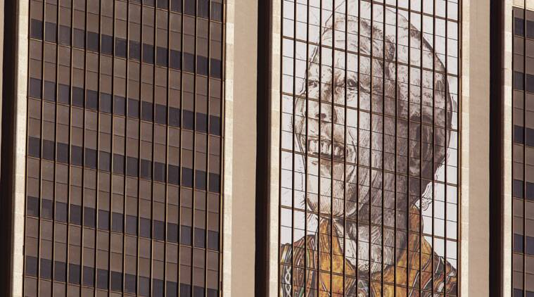 A mural of former South African President Nelson Mandela is placed on the wall of a building during his first dead anniversary in Cape Town, South Africa. (Source: AP photo)