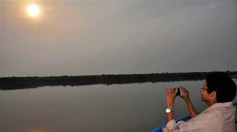 West Bengal Chief Minister Mamata Banerjee clicking picture of the setting sun during her trip for the promotion of Infrastructure cum Tourism Promotion to Jhorkhali, Sajnekhali in Sunderban area on Wednesday (Source: PTI)