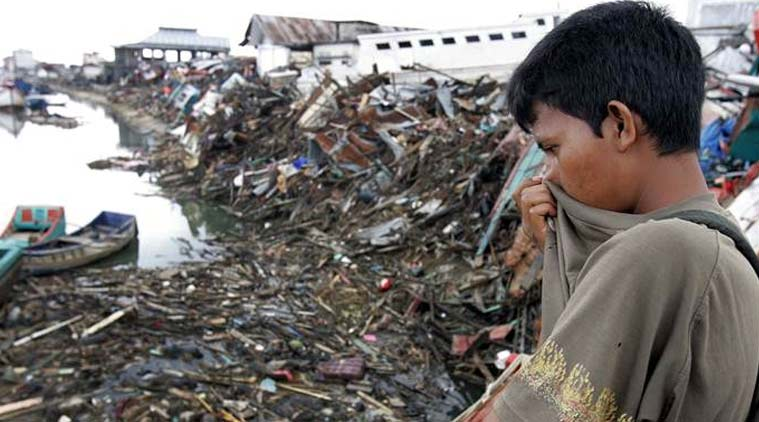 In this Saturday Jan. 1, 2005 file photo, a man looks at a floating debris and dead bodies on Aceh River in Banda Aceh, Indonesia. The tsunami that struck on Dec. 26, 2004, was one of the world's worst natural disasters in modern times. The tsunami that struck on Dec. 26, 2004, was one of the world's worst natural disasters in modern times. It followed a magnitude 9.1 earthquake that ruptured the sea floor off Indonesia's Sumatra island, displacing billions of tons of water and sending waves 10 meters (33 feet) high radiating across the Indian Ocean at jetliner speeds. Associated Press journalists who covered the story recall some of the most poignant images from the disaster. (Source: AP Photo/ File)