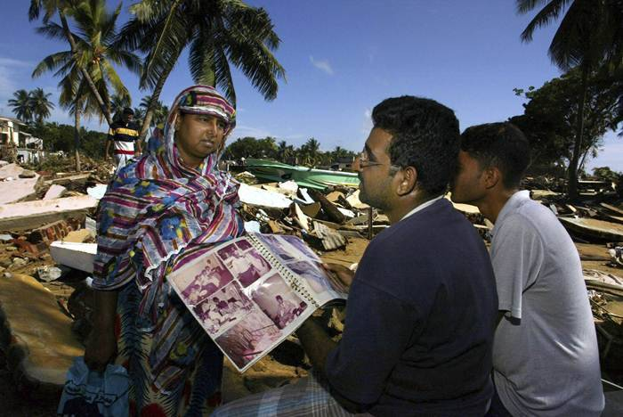 In this December 30, 2004 file photo, Hassan Fayez, center, speaks with one of his two surviving relatives, in what used to be his home as he holds a family album after losing 35 family members including his wife who was to deliver their first born son but died during the tsunami which hit the coastal town of Hambantota in southern Sri Lanka. Some 230,000 people were killed in the Indian Ocean tsunami set off by a magnitude 9.1 earthquake on Dec. 26, 2004. A dozen countries were hit, from Indonesia to India to Africa's west coast. Scores of Associated Press journalists covered the disaster, and as the 10th anniversary approached, the AP asked some of them to describe the images that have stuck with them the most. (AP Photo/Elizabeth Dalziel, File)