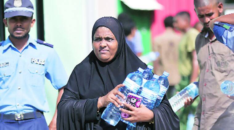 A woman carries water from a distribution centre in Male.