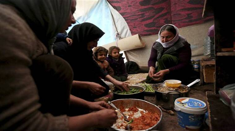 Yazidis displaced by Islamic State group militants share a meal as they take shelter in a partially constructed building in Dohuk, northern Iraq. (Source: AP)
