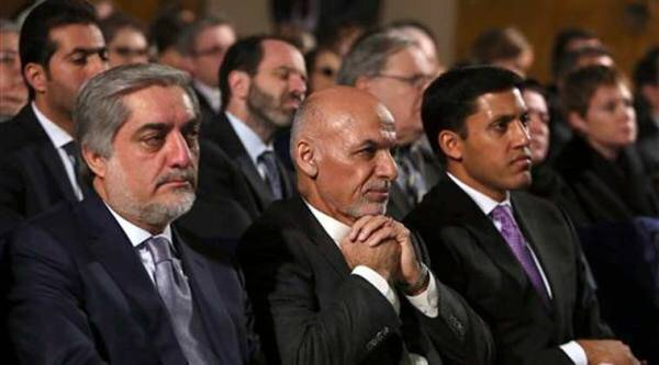 In this file photo taken Saturday, Nov. 8, 2014, Afghanistan's President Ashraf Ghani, center, sitting next to Chief Executive Abdullah Abdullah, attends an event for the Afghan Women's Empowerment Grants Program in Kabul, Afghanistan.