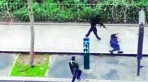 The two gunmen shoot a security officer in front  of the magazine's office. (Source: Reuters)