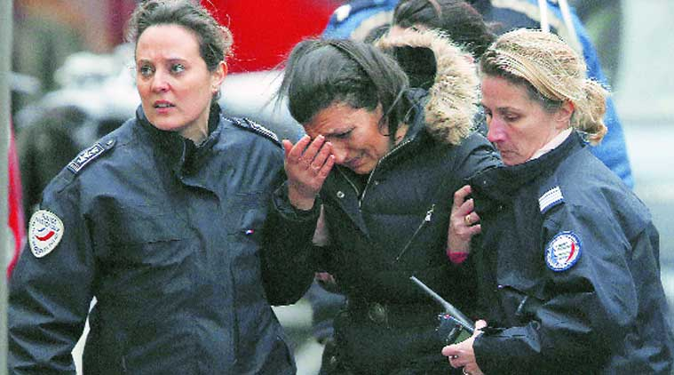 Police console a woman at the scene of a shooting in which a policewoman was killed, in the street of Montrouge near Paris. (Source: REUTERS)