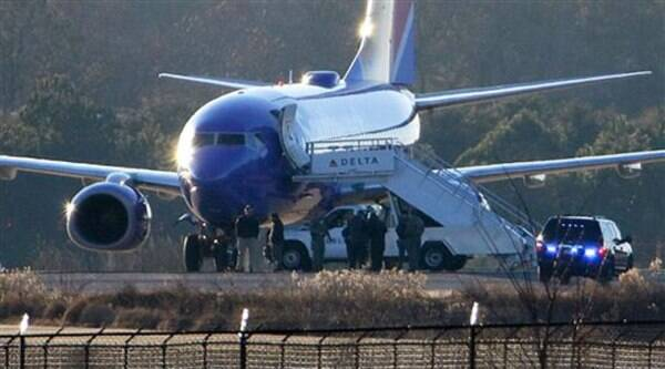 """Law enforcement officials stand beneath a Southwest Airlines airplane on the tarmac at Hartsfield-Jackson Atlanta International Airport, Saturday, Jan. 24, 2015, in Atlanta. Police were searching two planes at Atlanta's main airport after authorities received what they described as """"credible"""" bomb threats. (AP Photo)"""
