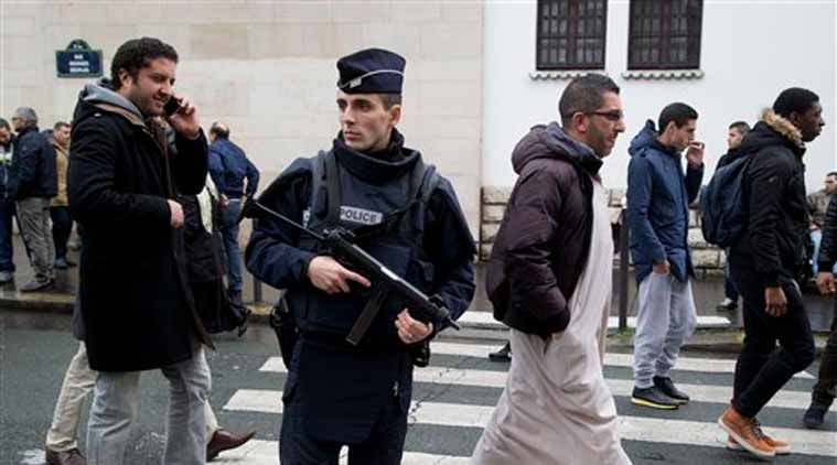 In this photo,  a French police officer stands guard outside the Grand Mosque as people arrive for Friday prayers, Paris. (Source: AP)