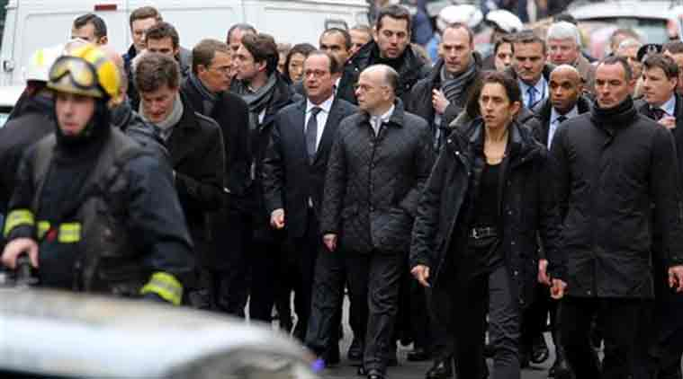 French President Francois Hollande, center left, flanked with French Interior Minister Bernard cazeneuve, right, walk outside the French satirical newspaper Charlie Hebdo's office, in Paris, Wednesday (Source: AP)