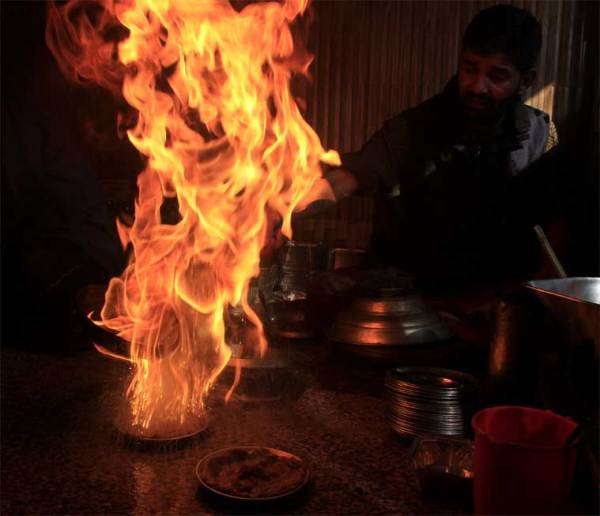 The flames rise as sizzling oil is poured on the harisa to bring out its delectable flavours (Source: IANS/Kamran Rashid Bhat)