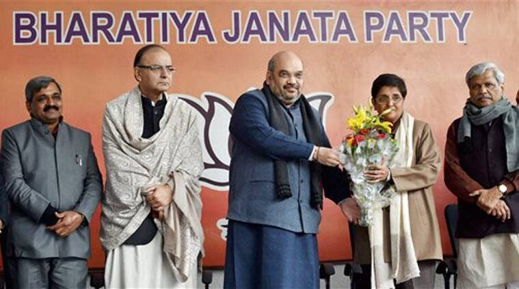 BJP President Amit Shah presents a bouquet to former IPS officer Kiran Bedi to welcome her into the party as Union Minister Arun Jaitley and Delhi BJP President Satish Upadhyay look on during a press conference in New Delhi on Thursday.  (Source: PTI)