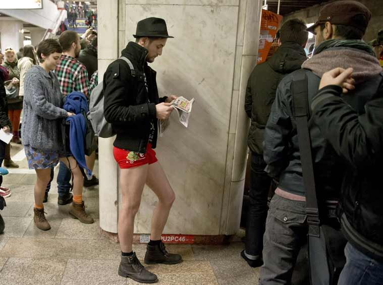 """A man reads a newspaper as he takes part in the first edition of the No Pants Subway Ride in Bucharest, Romania, Sunday, Jan. 11, 2015. The No Pants Subway Ride began in 2002 in New York as a stunt and has taken place in cities around the world since then. Organizers call it """"an international celebration of silliness"""" and are organizing it in dozens of cities on Sunday. (AP Photo/Vadim Ghirda)"""