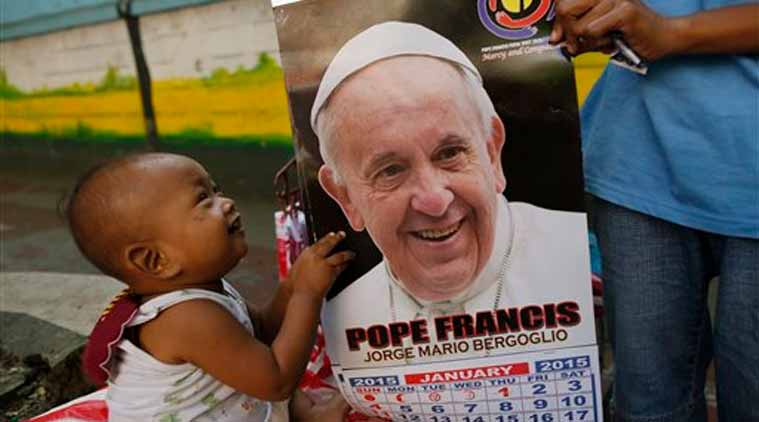 Filipino baby Vincent holds on to a calendar of Pope Francis as his mother Flor, 20, tries to sell souvenirs along the Pope Francis motorcade route in Manila, Philippines, Thursday. (Source: AP)