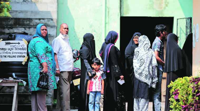 Voters stand in a queue outside a polling station in Colombo. (Source: AP)