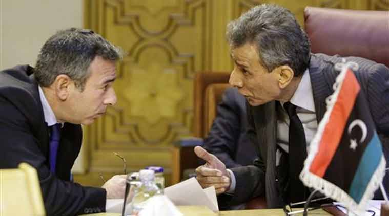 Libyan representative at the Arab League Ashour Abu-Rashed, right, talks to his Egyptian counterpart Tarek Adel, during an emergency representatives meeting to discuss the conflict in Libya, at the Arab League headquarters in Cairo, Egypt, Monday. (Source: AP)