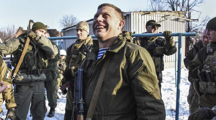 In this Thursday, Jan. 15, 2015 photo, Pro-Russian rebel leader Alexander Zakharchenko, center, surrounded by guards, smiles not far from rebel positions near the Donetsk airport in Donetsk, Eastern Ukraine. Russian-backed separatists announced Thursday they had captured the shattered remains of the Donetsk airport terminal and plan to claw back more territory, further dashing hopes for a lasting peace agreement. (AP Photo/Mstyslav Chernov)
