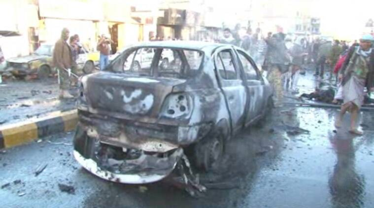 n this framegrabbed image from footage shot by AP Television News, a damaged car sits in the road after a suicide bomber driving a minibus full of explosives killed more than a dozen people Wednesday morning near a police academy in the heart of Yemen's capital, Sanaa, security officials said Wednesday Jan. 7, 2015. The blast wounded dozens more, officials said (AP Photo)