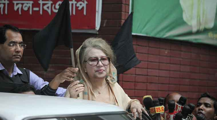 Bangladesh's former PM Khaleda Zia holds a black flag as she stands at her office in Dhaka on Monday. (Source: AP photos)