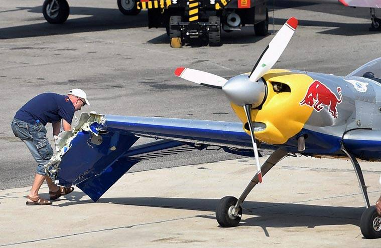 A technician of red bull aerobatic team inspects the wing of the aircraft after its clash with the other the aircraft while performing. (Source: PTI)