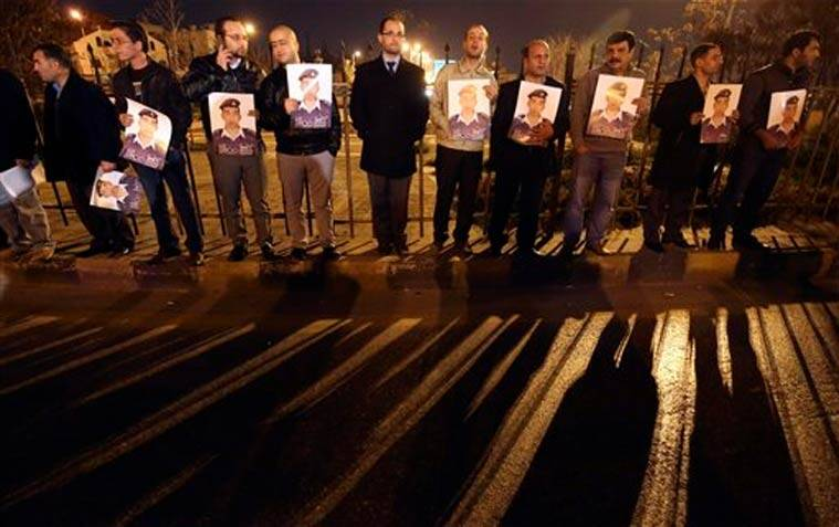 activists hold up pictures of Jordanian pilot Muath al Kasaesbeh during a sit-in solidarity with him in Amman, Jordan.