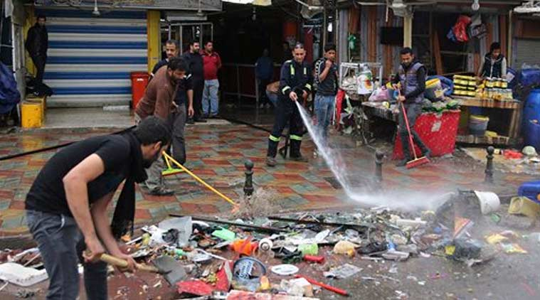 Baghdad municipality workers help clean up the site of a suicide bombing that targeted a street filled with hardware stores, killing over 20 people and wounding at least 45, in the Iraqi capital's southeastern neighborhood of New Baghdad. (Source: AP photo)