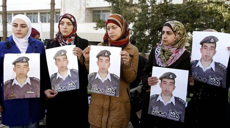 "Anwar al-Tarawneh, center, the wife of Jordanian pilot, Lt. Muath al-Kaseasbeh, who is held by Islamic State group militants, holds a posters of him with Arabic that reads, ""we are all Muath,"" during a protest in Amman, Jordan. (Source: AP)"