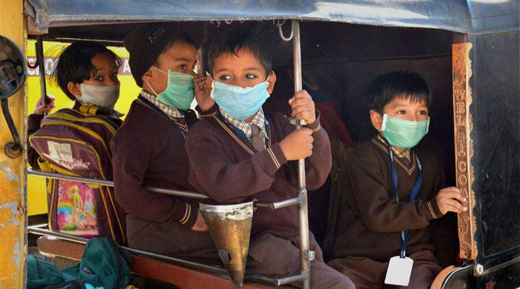 Children in an Auto rickshaw with their faces covered with masks as a preventive measure against Swine flu, which has claimed more than 19 lives in Ajmer, Rajasthan. (Source: PTI)