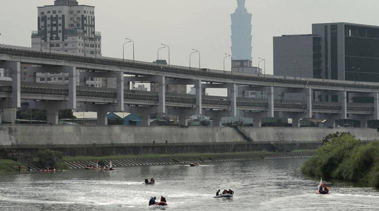 With the iconic Taipei 101 building in the background, divers on boats look for missing passengers of crashed TransAsia Airways Flight 235 in a river in Taipei, Taiwan, Saturday, Feb. 7, 2015. All 71 pilots who operate TransAsia Airways' ATR propeller-jets began proficiency tests on Saturday, three days after one of the carrier's ATRs crashed into the river. (AP Photo/Wally Santana)