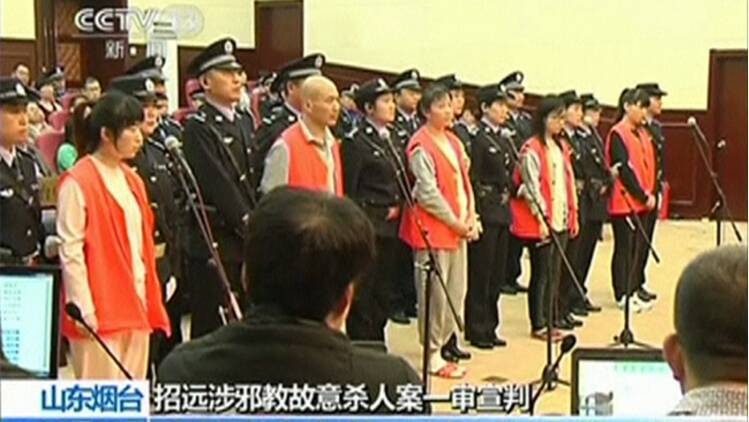 Defendants stand with police escorts during their trial for the murder of a woman at a McDonald's restaurant, in Yantai City, Shandong province October 11, 2014 in this still image taken from video. (Reuters)