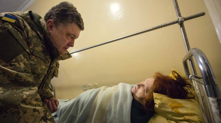 Ukrainian President Petro Poroshenko, left, talks with a wounded victim of an artillery strike in a Kramatorsk hospital, Donetsk region, Ukraine, early Wednesday, Feb. 11, 2015. (AP Photo)