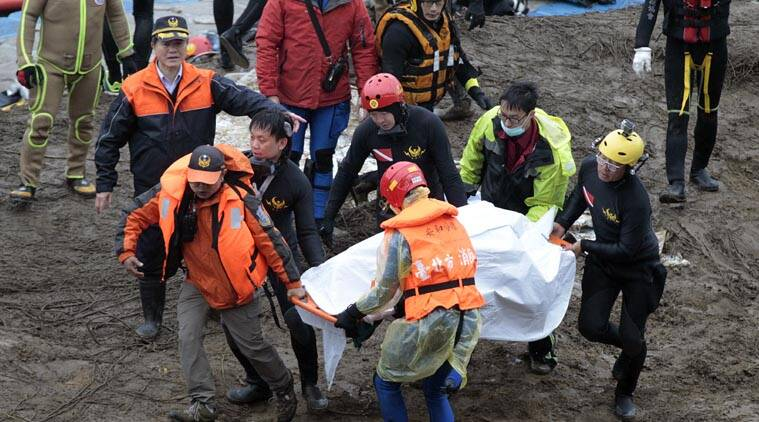 Search and rescue divers carry a recovered body at the site of a commercial plane crash in Taipei, Taiwan, Friday, Feb. 6, 2015. (AP Photo)