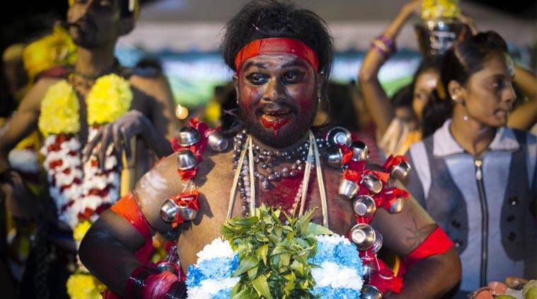 FILE- A Hindu devotee has milk pots hooked on his body as he gets ready for his pilgrimage walk during the Thaipusam festival. (AP Photo)