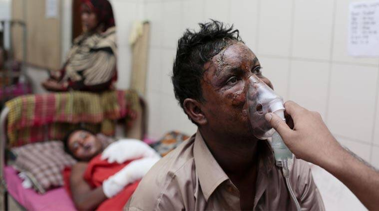A relative holds an oxygen mask on Mohammad Hanif, 35, victim of a firebombing, at a hospital in Dhaka, Bangladesh, Thursday, Feb. 5, 2015. (AP Photo)