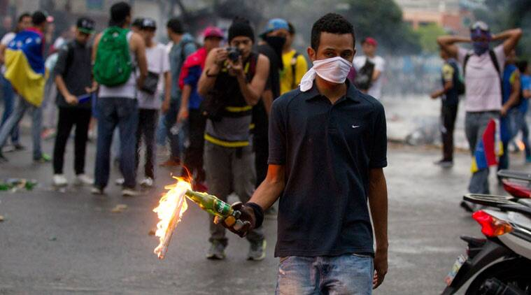 An opposition demonstrator prepares to throw a molotov cocktail at police after clashes broke out at a protest in Caracas, Venezuela, Thursday, Feb. 12, 2015. Venezuelans staged dueling marches to mark the anniversary of last year's bloody protest movement that resulted in more than 40 people being killed, including both government supporters and opponents. Dozens of protesters remain jailed, while the social issues they railed against last year- a faltering economy, widespread shortages and pervasive violent crime - have only gotten worse. (AP Photo/Fernando Llano)