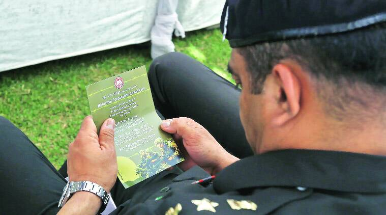 An Army officer looks at the invitation card with pics of American soldiers. (Express photo by Sumit Malhotra)