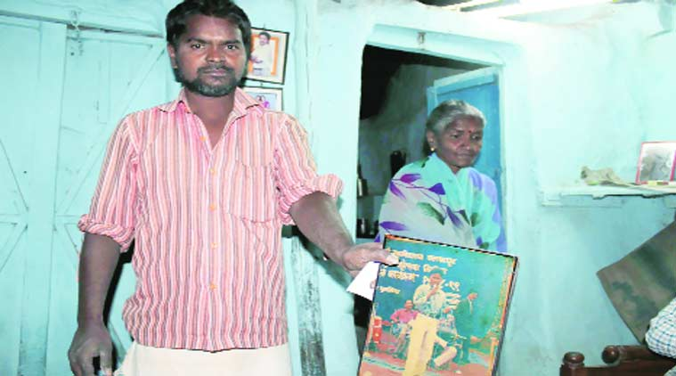 Arun Bhelke's brother shows a photograph of the arrested 'Maoist' at their Ambedkar Ward residence in Ballarsha, Chandrapur. (Source: Express Photo byChandan Haygunde)