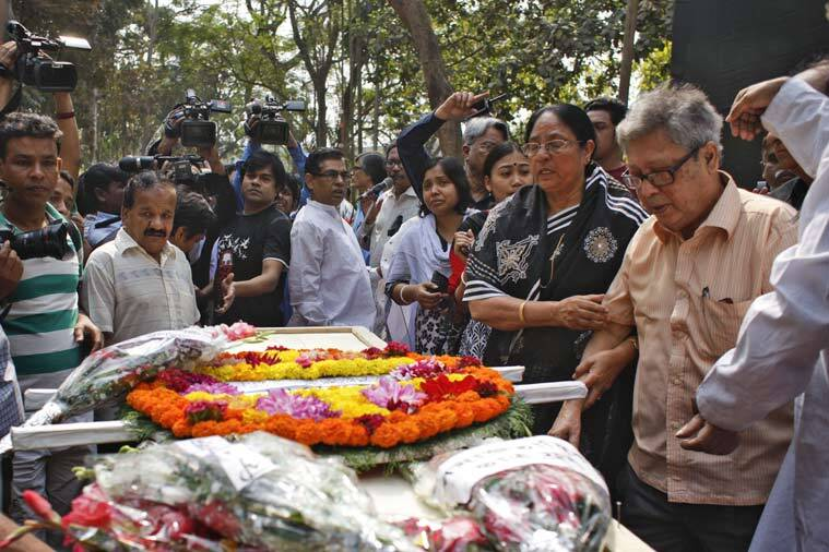 Father Ajay Roy, right, stands beside the coffin of Avijit Roy, in Dhaka, Bangladesh on Sunday. Roy, known for speaking out against religious extremism was hacked to death Thursday night as he walked through Bangladesh's capital with his wife, police said Friday.(Source: AP)