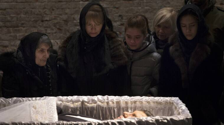 Relatives and friends pay their last respects while passing the coffin of Boris Nemtsov, a charismatic Russian opposition leader and sharp critic of President Vladimir Putin, during a farewell ceremony inside the Sakhavov's center in Moscow, Russia, Tuesday, March 3, 2015. Mourners are lining up outside the Moscow human rights center for the funeral of murdered Nemtsov. Western officials have called for Russia to conduct a prompt, thorough, transparent and credible investigation into the slaying. Putin has ordered law enforcement chiefs to personally oversee the probe. (Source: AP)